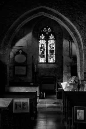 Looking down the length of the church from the altar. There is a stained-glass window on the back wall and carved memorials on the wall. The church is dark, with parts lit up by sunlight coming through the door and windows