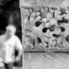 A carving of a plant (acanthus?) on the corner of the vestry. To the left, a man (out of focus) can be seen walking towards the camera)