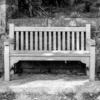 "A wooden bench by the graveyard. On the back of the bench is an inscription, reading ""rest and be thankful"""