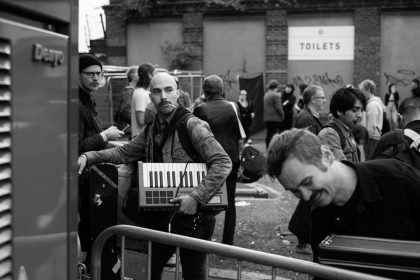 A man with a shaved head is carrying a small keyboard and is looking over his shoulder. Next to him is a man looking down at something and smiling. There are people around them as it's a music festival