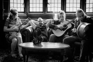 The four musicians sitting on a sofa and stools. Gary is looking at the camera, with his feet up on a low table and his hands behind his head. The other three are playing their instruments and looking away from the camera