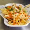 A portion of fries with toppings such as spring onions, hot sauce and blue-cheese sauce, in a shallow, rectangular tray