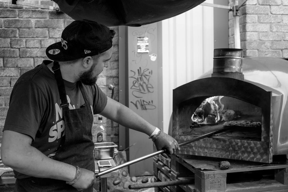 A man putting a pizza into a wood-fired oven