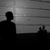 Silhouettes of two people in a warehouse listening to music