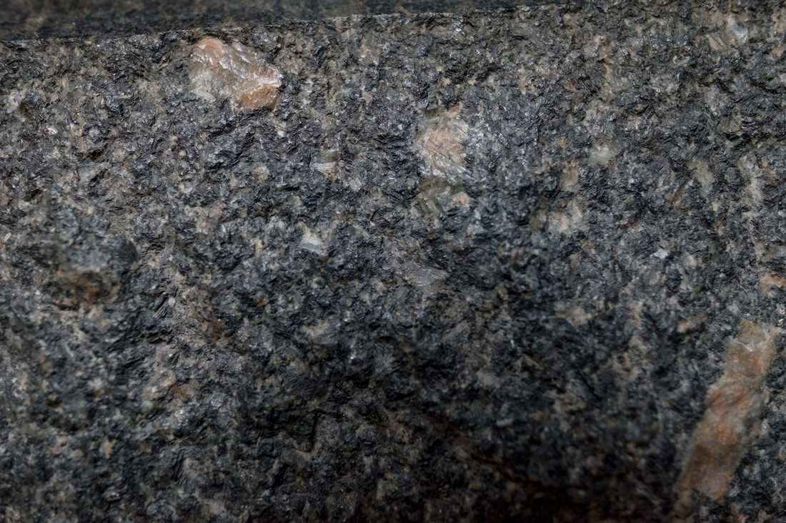 A closeup of the worn surface of a black granite stateu