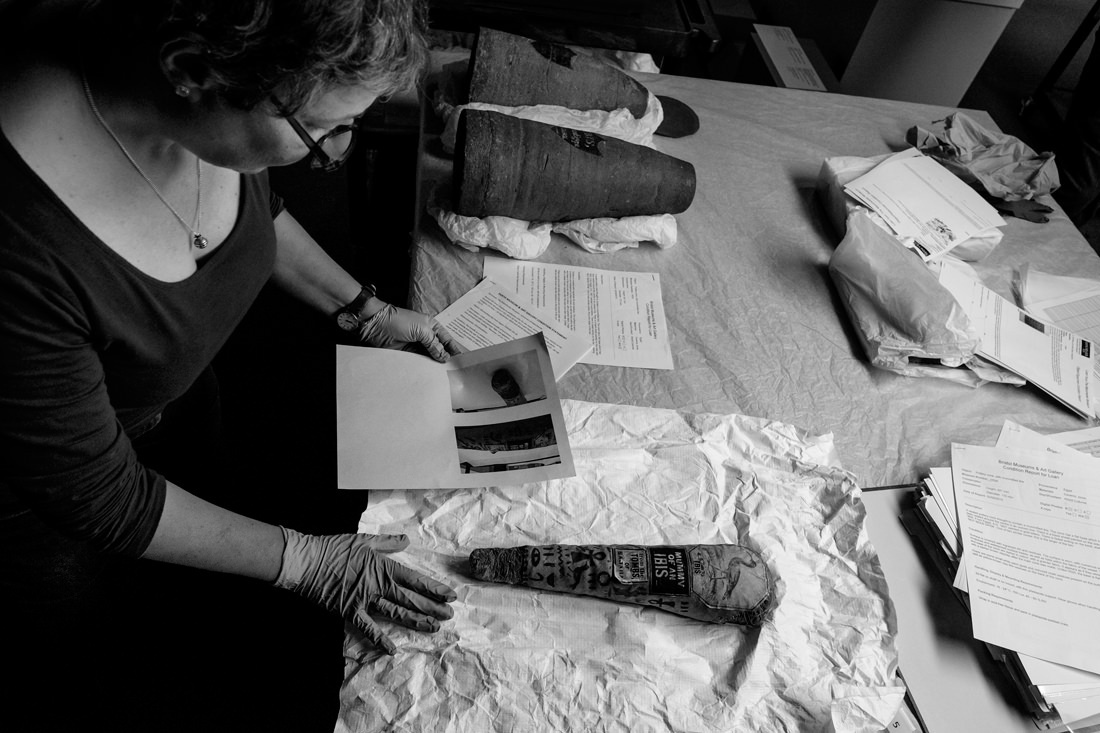A conservator inspecting a mummified animal