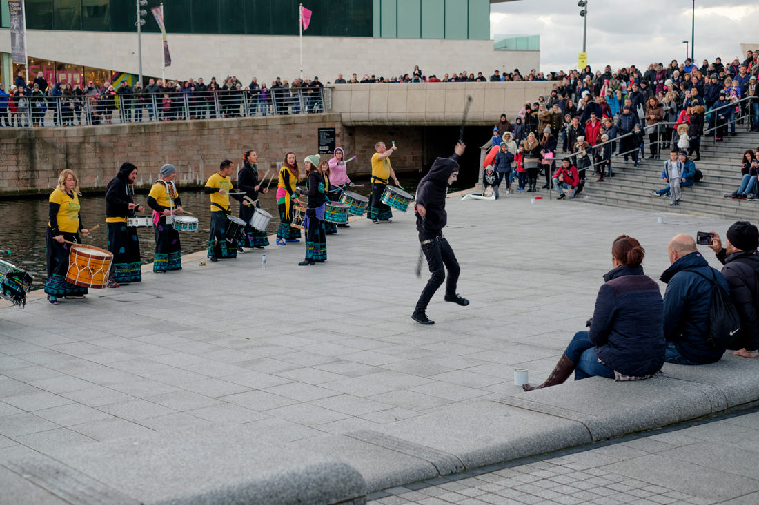 The drummers with a fire dancer in front of them. Crowds of onlookers surround them.