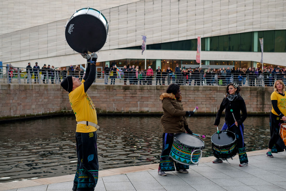 A drummer is beating his drum as he hurls it up into the air above his head