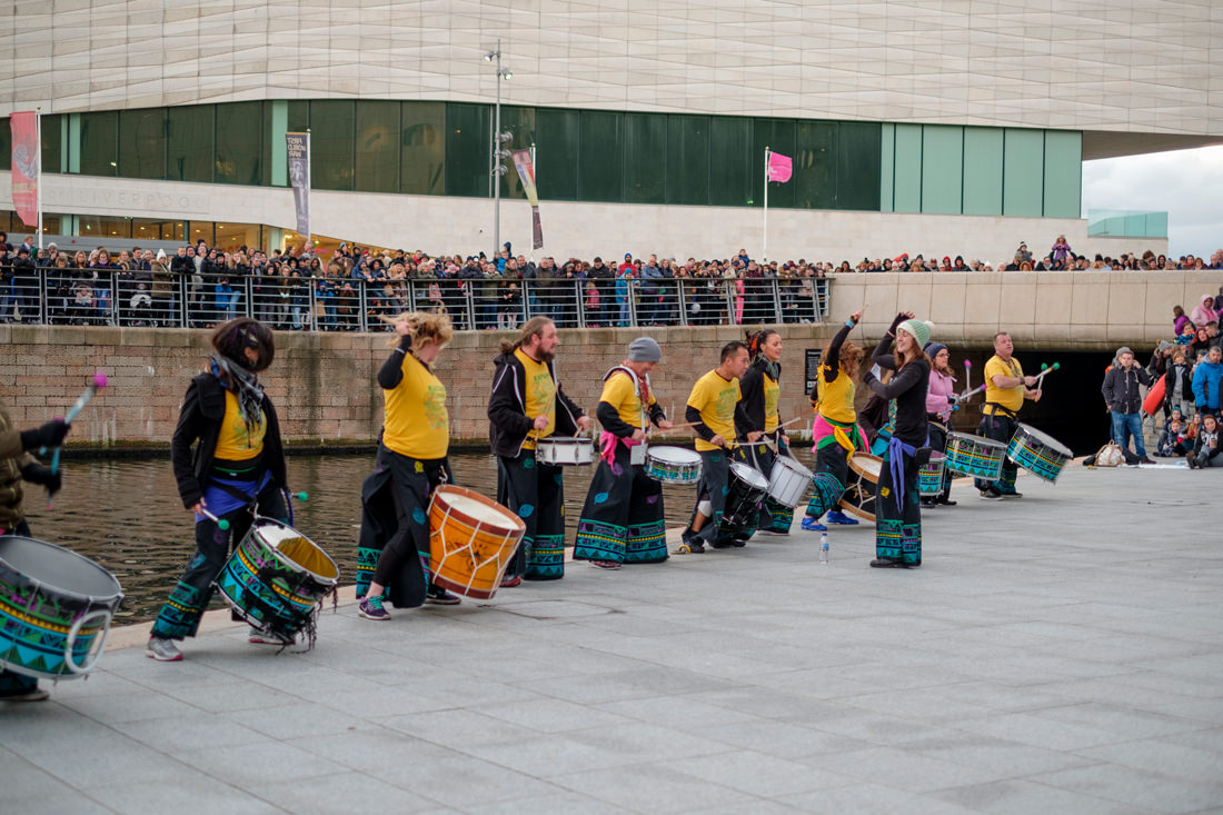 A row of people with drums, with crowds of people of around them. The drummers are dancing and getting into the beat