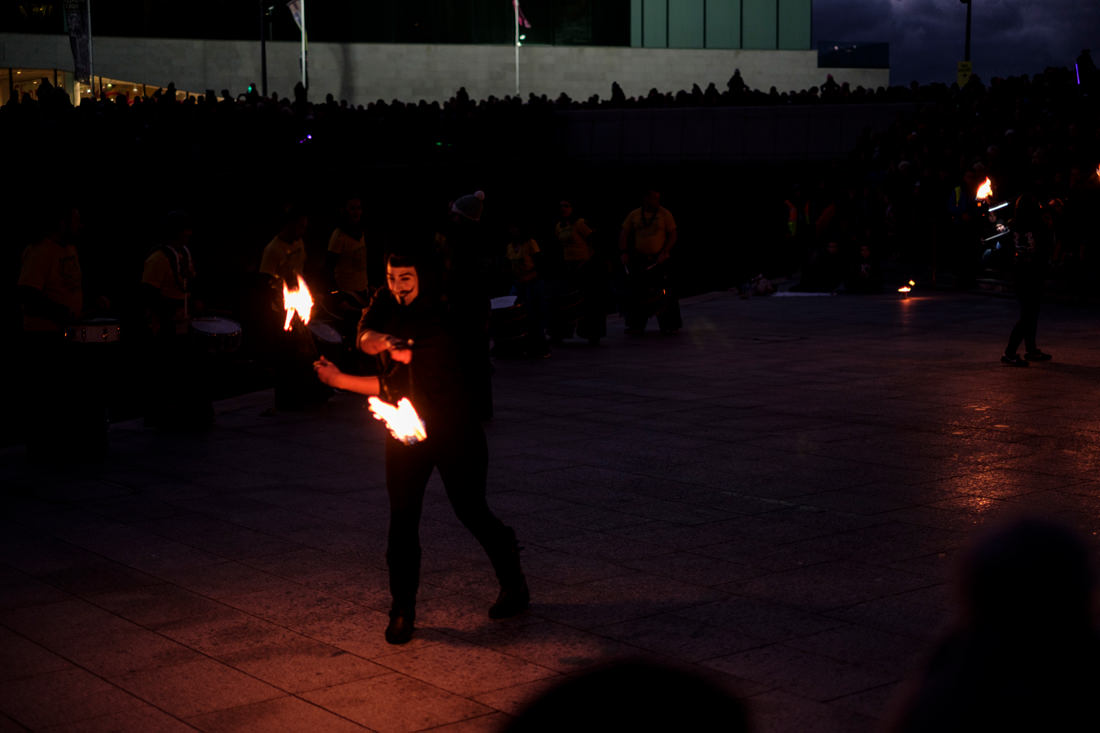 The firedancers, now in the dark, with their fire sticks lit.
