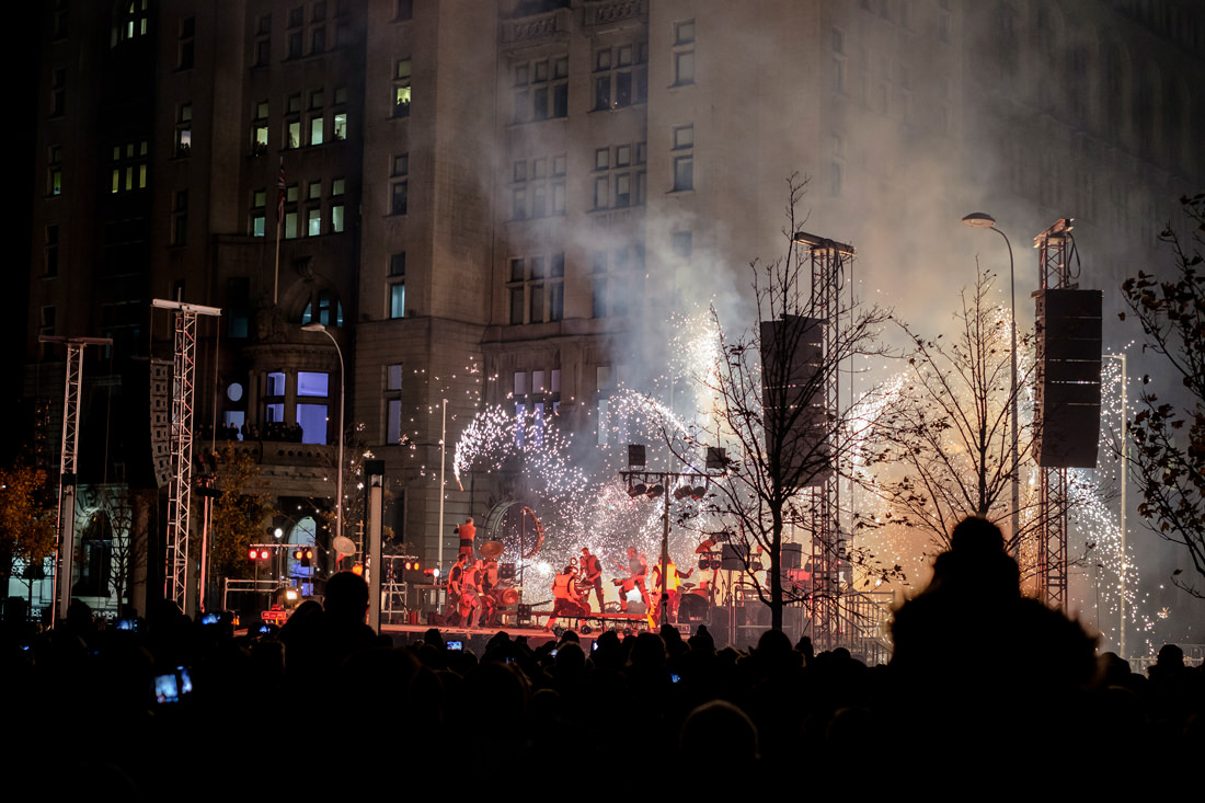 a group of drummers, all dressed up, on stage, with fireworks going off behind them