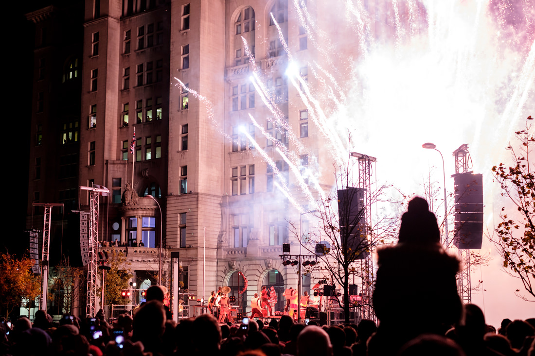 The drummers in front of the Liver Building with an explosion of fireworks going off