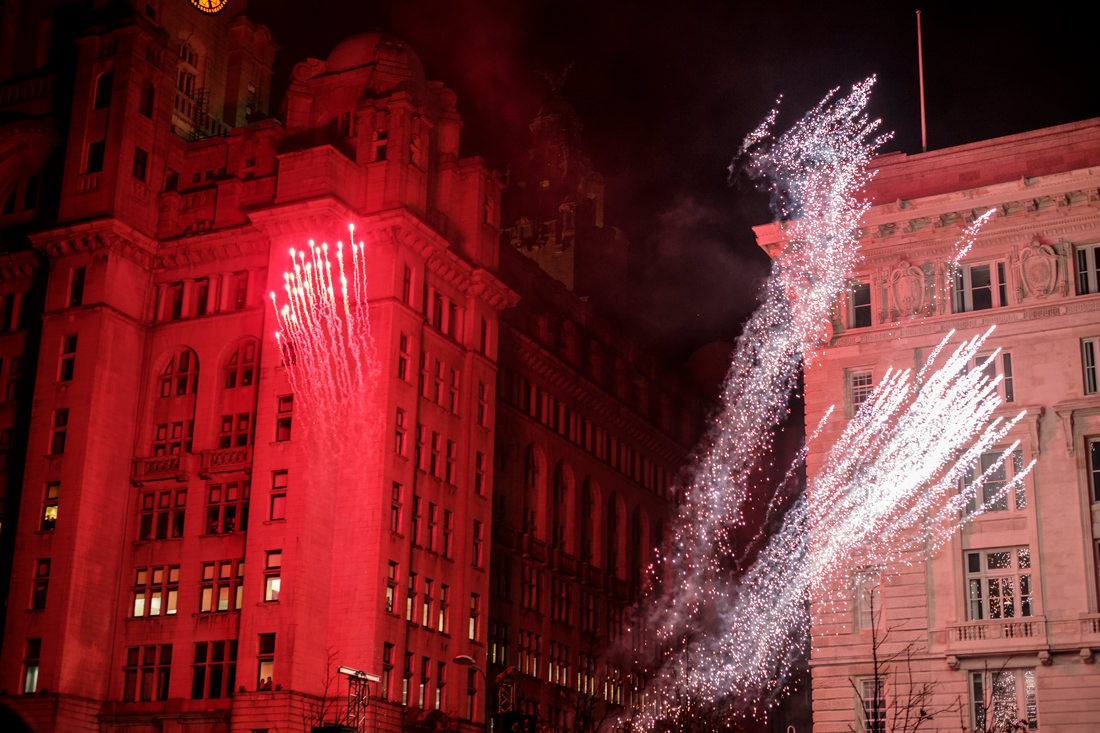 The front of the Liver Building and Cunard Building lit up by fireworks