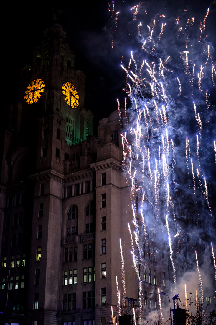 The tower and clock of the Liver Building with fireworks shooting up by the side of it
