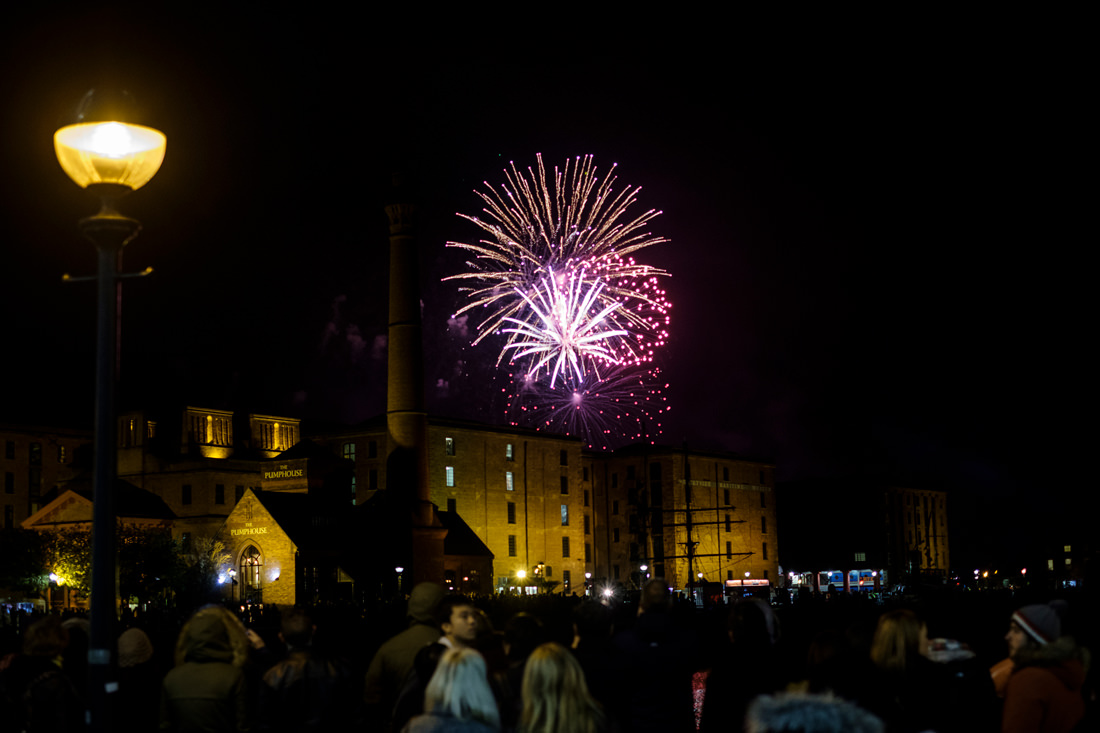 Fireworks exploding in the air behind the Albert Dock