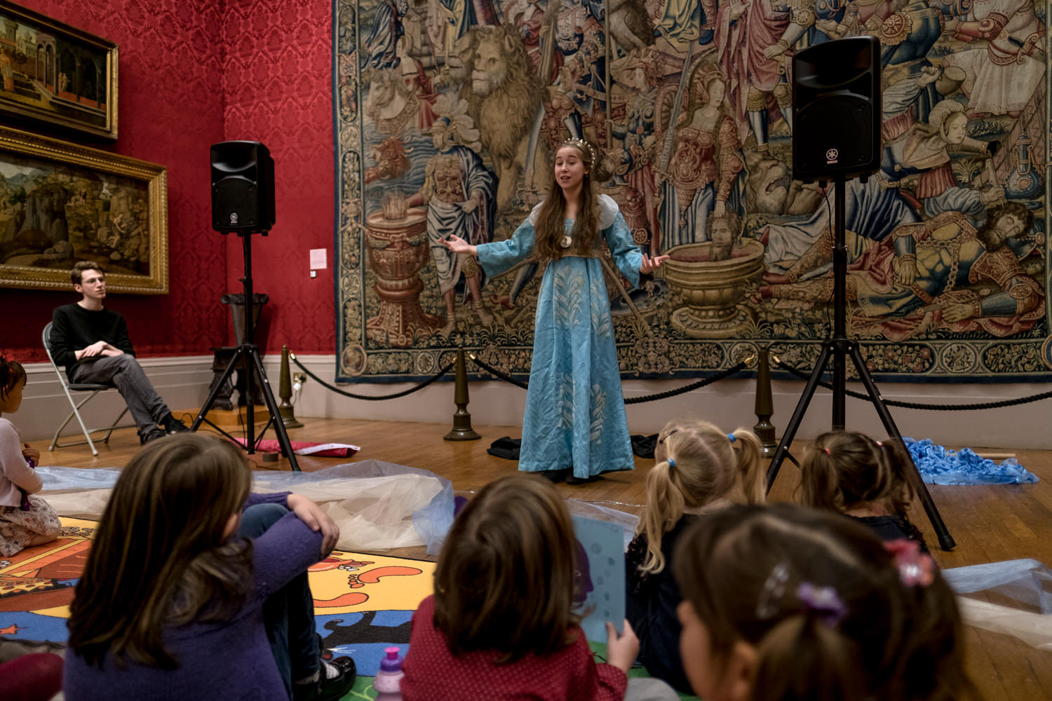 An actress in a long, blue, medieval-style dress standing in a gallery in front of a large, ancient tapestry. She's performing in front of an audience with some children sitting on the floor in front of her