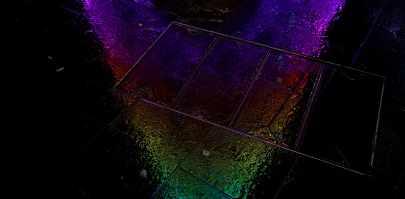 A reflection of the colourful Christmas tree on the wet pavement