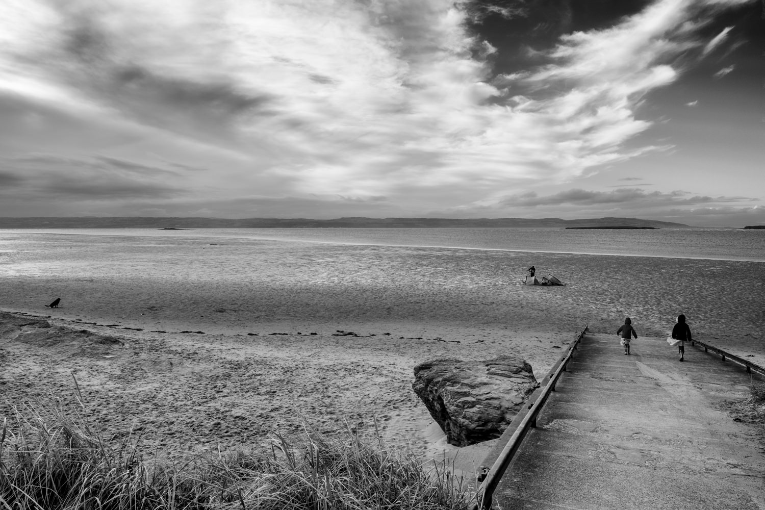 Looking across a sandy beach towards the sea. The North Wales coast is visible across the sea and the sky has dramatic clouds. There are two girls walking on to the beach