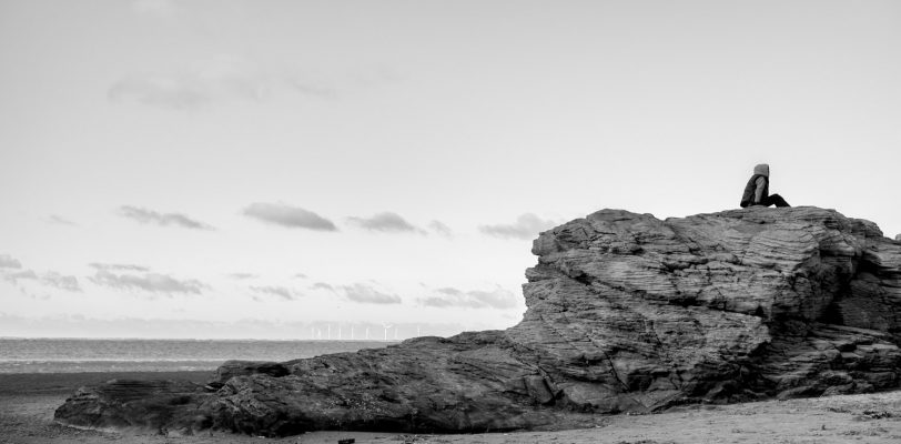 A boy sitting on top of a rocky outcrop, sitting side on to the camera. In the distance a wind farm can be seen out at sea