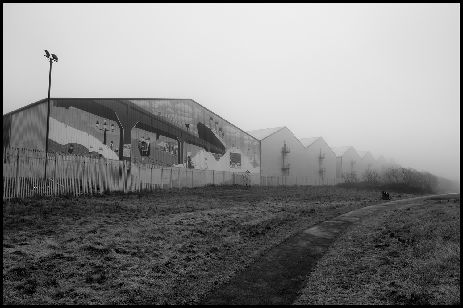 The warehouses at the end of the docks disappearing into the fog