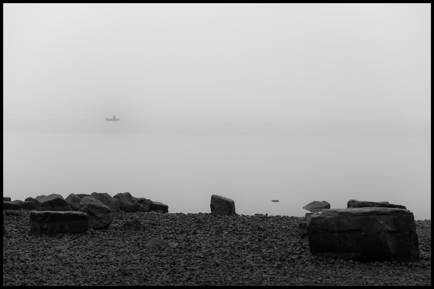 A person on a boat on the lake is just visible in the fog. In the foreground are rocks and shale