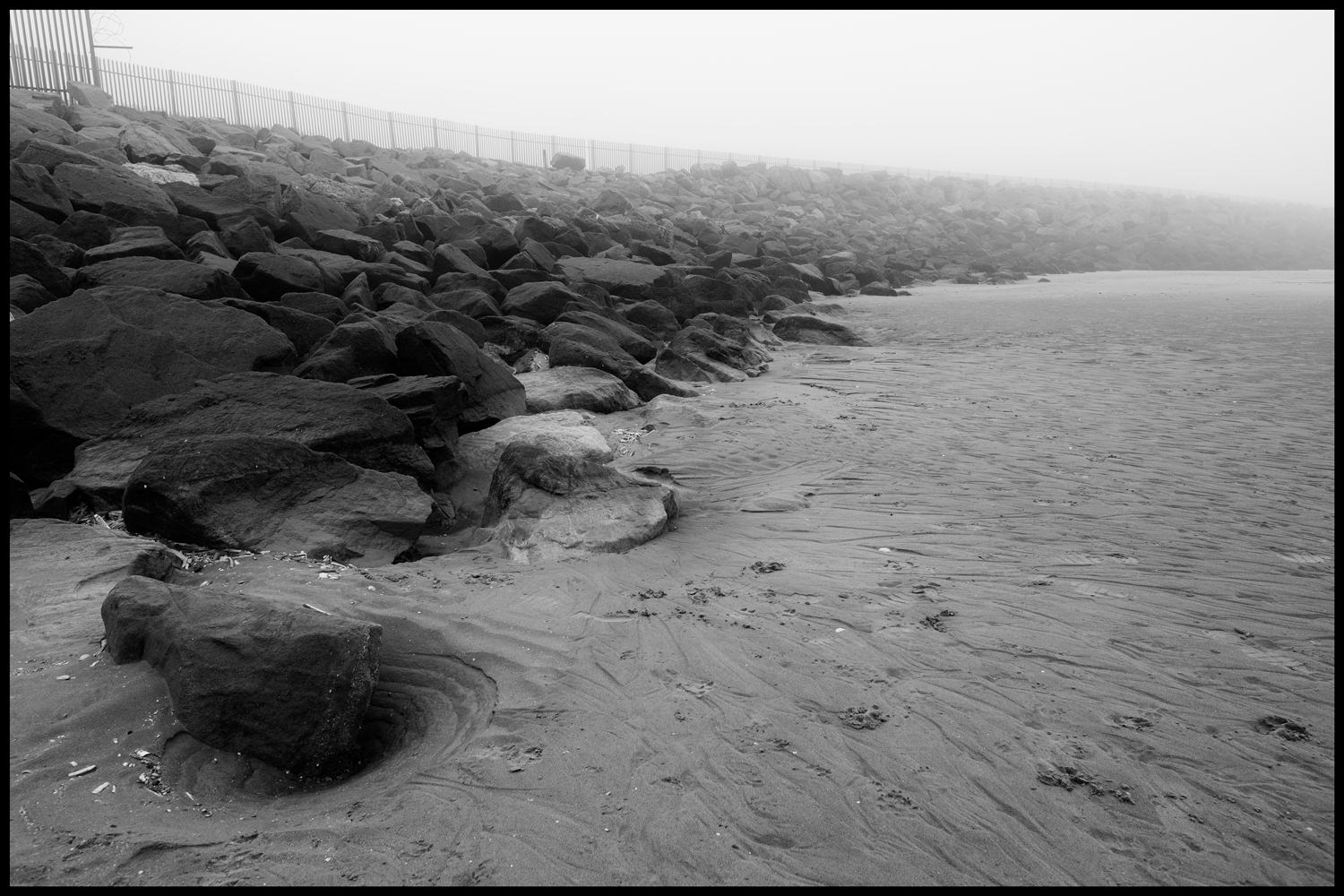 Sand and rocks on the beach. The pile of rocks is disappearing into the fog and there are lots of swirls and patterns in the sand from where the tide goes in and out