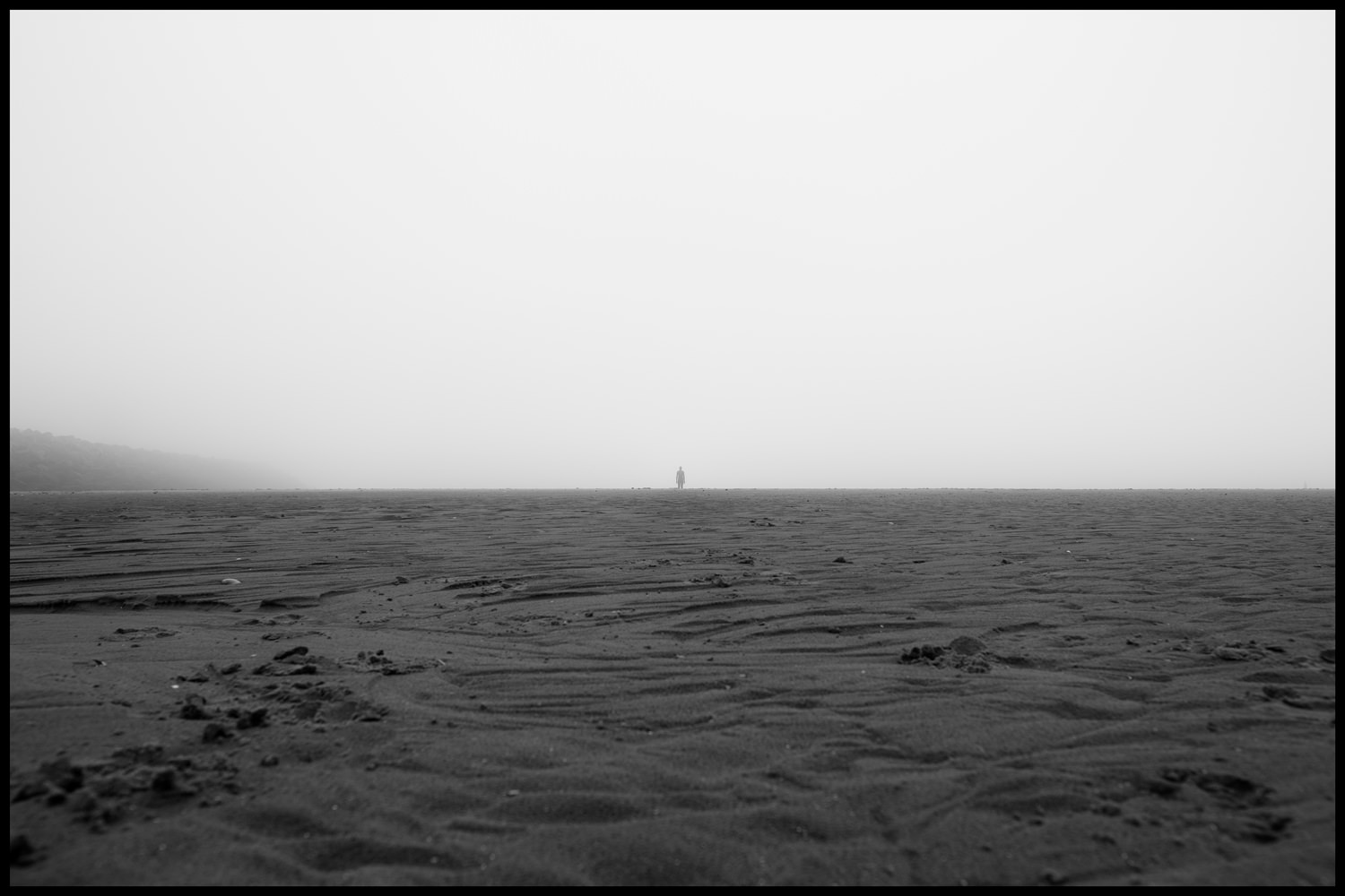 One of the iron men statues on the horizon with an expanse of sand in the foreground