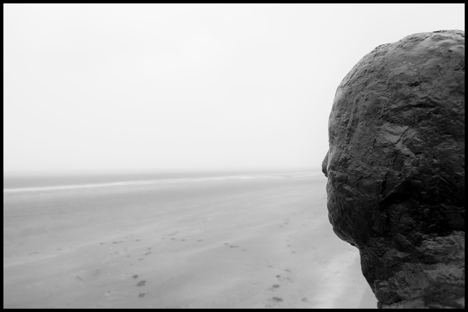 Looking down the foggy beach with the head of one of the iron men in the foreground. The camera is looking three-quarters on to the head from behind it