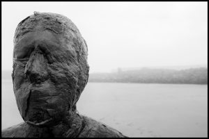 Looking straight on to the face of one of the iron men with the beach in the background