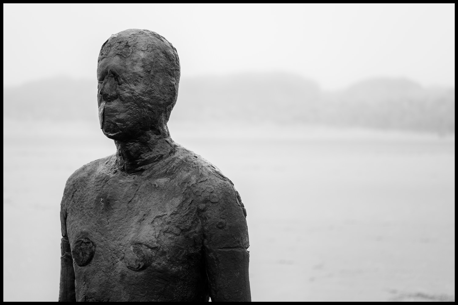 The top half of one of the iron men, from the front, with the beach in the background, fading into the fog