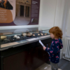 A young girl standing in front of a display case of ancient objects. She's looking at a piece of paper with a treasure hunt on it
