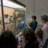 Six children in front of a display case in the museum, looking for objects