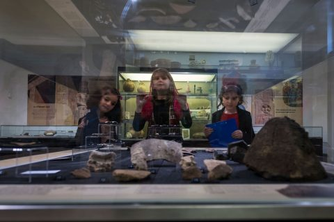 Three girls next to a glass display case. The camera is looking through the glass from the other side of the case at the girls