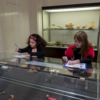 Two girls at a glass display case. They're writing on pieces of paper
