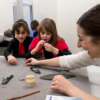 The museum curator is showing small, Egyptian objects to some children