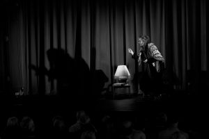 A woman on a stage dressed up as an old woman, talking to the audience