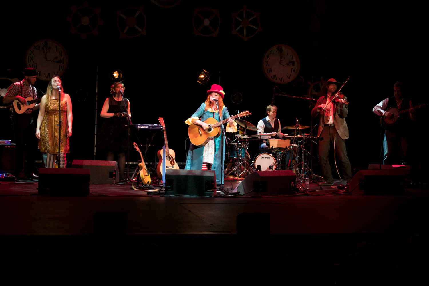 A group of musicians on stage. The light is focused on a woman in a blue overcoat and red top hat, playing a guitar and singing