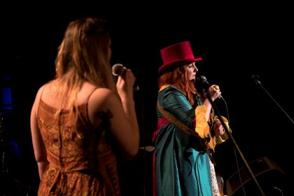 Two women on stage, singing. One is in profile and the other has her back to the camera