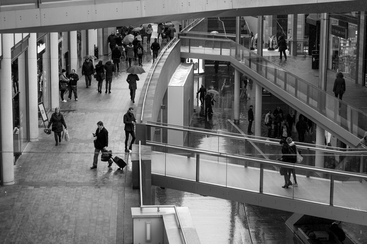 Looking down into the Liverpool One shopping centre. There's lots of people with umbrellas and bags
