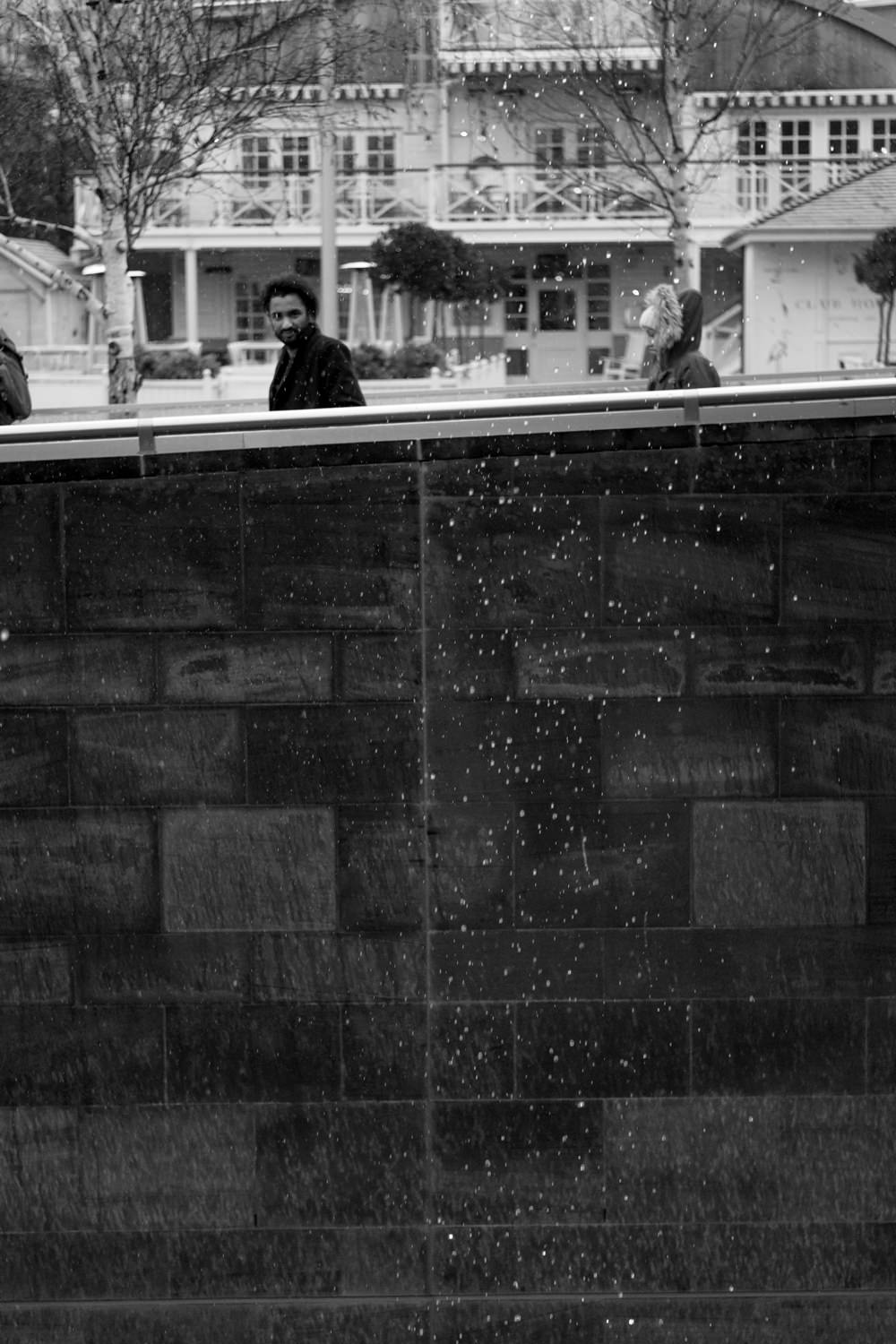 Two people walking past a cascade of water droplets