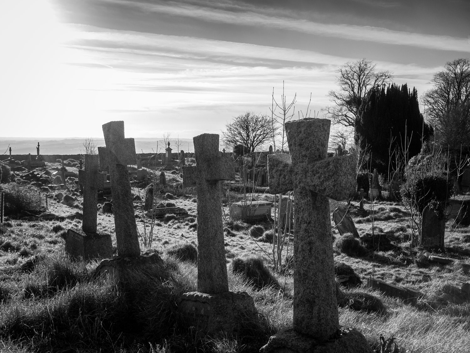 Looking across Lansdown cemetery. In the foreground are three graves with near-identical, plain stone crosses