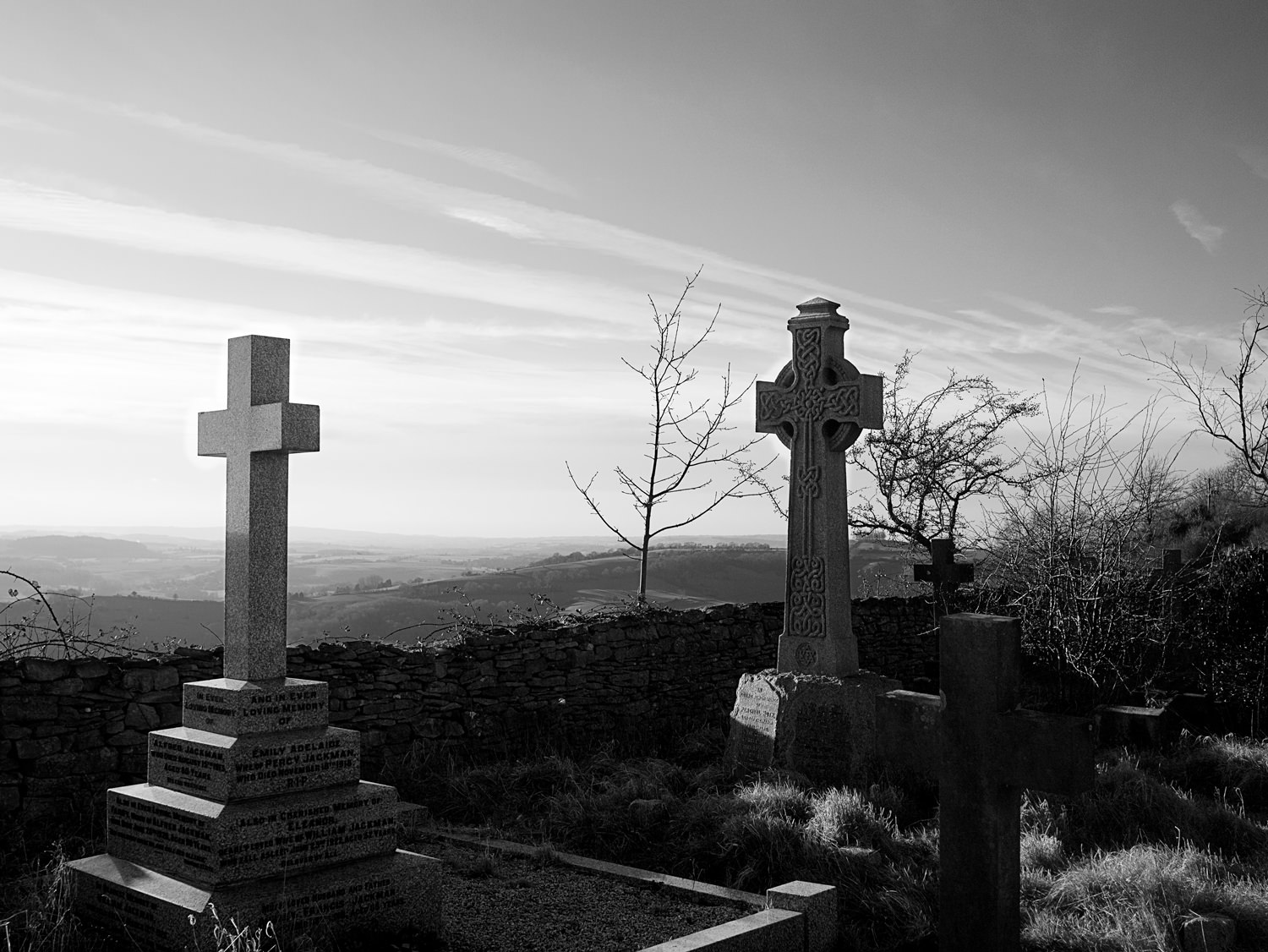At the edge of Lansdown cemetery, looking over a low, stone wall, the valley stretches out as far as the eye can see. In the foreground are two graves with tall crosses. One cross is plain and the other is ornate, in the style of ancient Celtic crosses