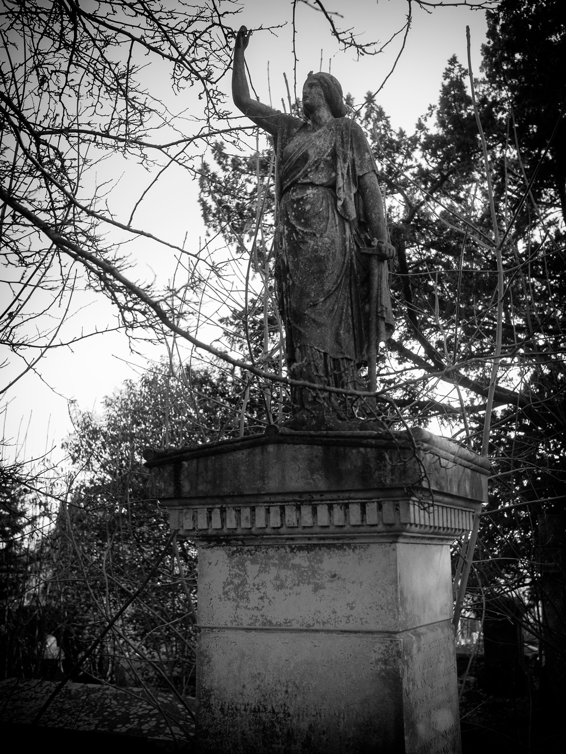 A statue in a typically Victorian, neo-classical style. The statue is a woman in draped clothes, with one arm up in the air.