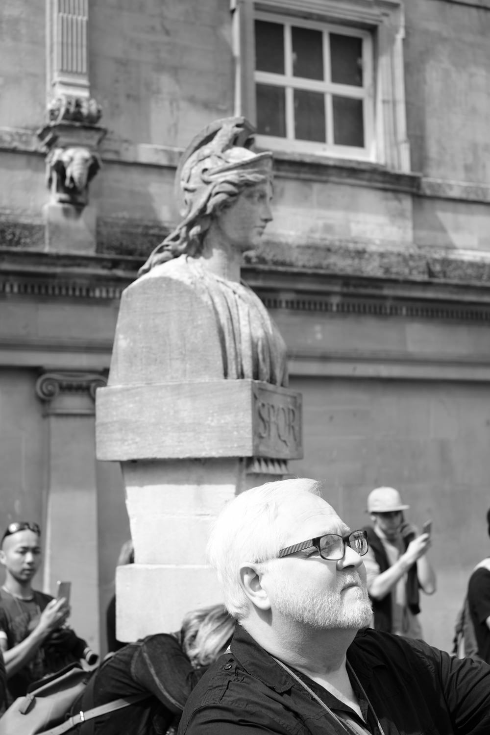 A man standing in front of a 19th century statue of a Roman man with 'SPQR' inscribed at the bottom.