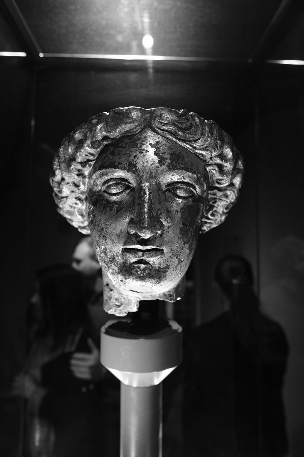 A cast-metal head of a woman in typical Roman style.