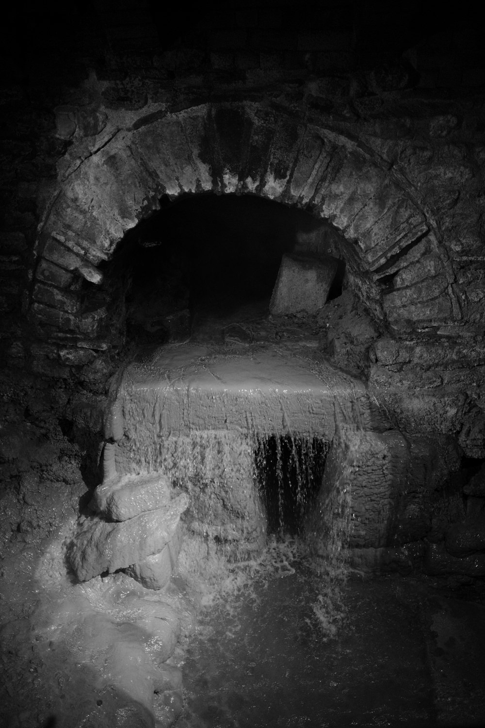 A semi-circular tunnel with water pouring out of the end.