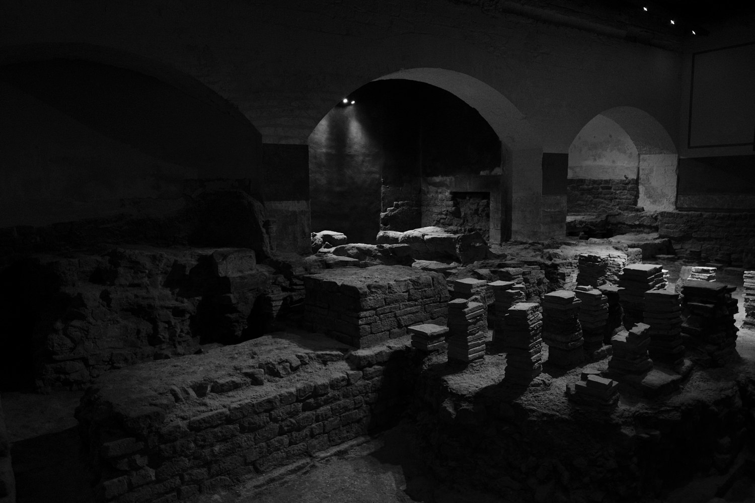 A room with circular archways. The floor is missing parts, showing the stacks of bricks used to make the hypercaust.