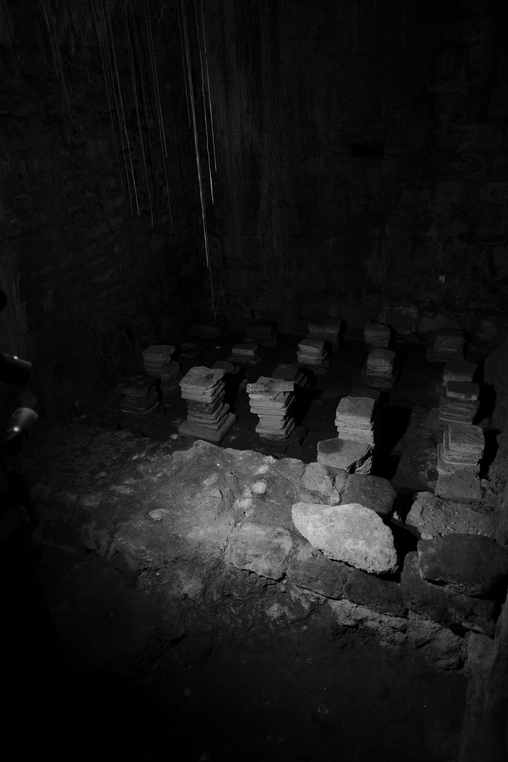 Another corner of a hypercaust system. The room is dark, with just a few stacks of bricks showing.