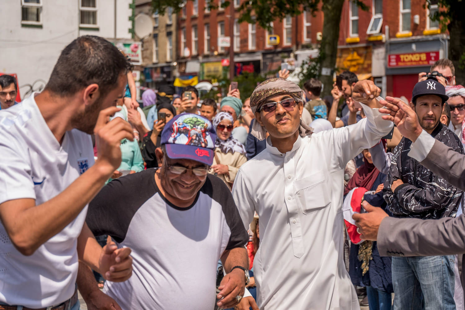 A crowd of people. Three men, one in traditional Arab clothes, are dancing and smiling.