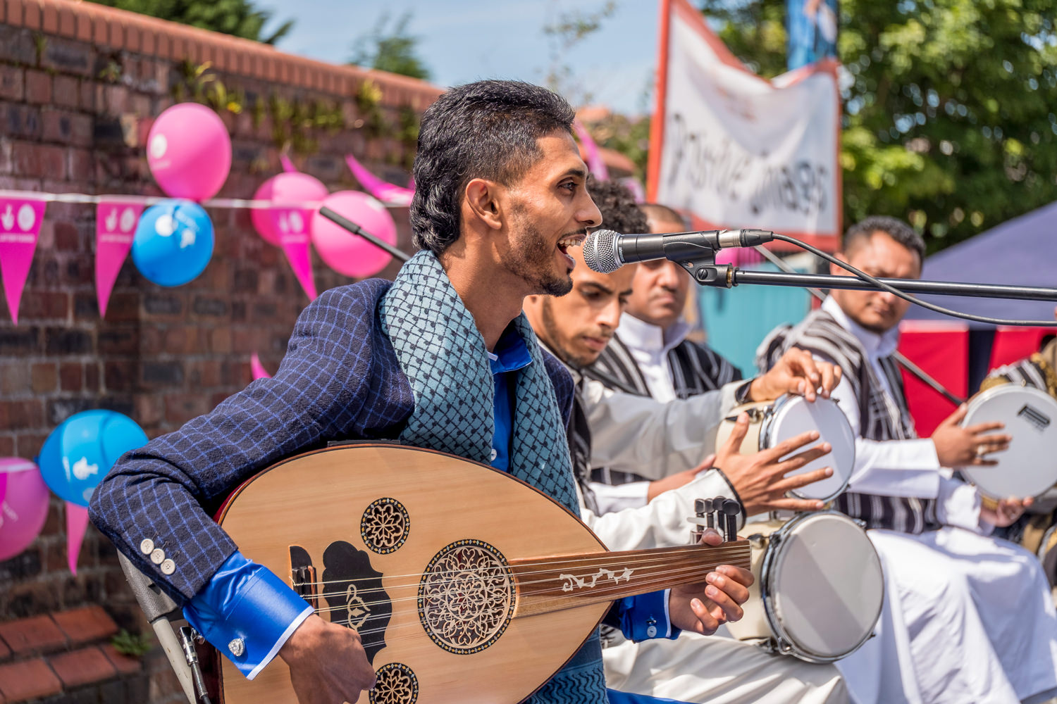 A traditional Arabic music group. Five seated men in front of a red-brick wall. Only the nearest man is in focus. He's singing into a microphone and playing an oud, a traditional Middle Eastern stringed instrument.